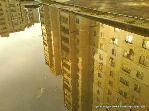 Отражение многоэтажного дома в луже